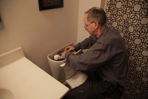 Plumber Working on Toilet - Northwest Plumbing